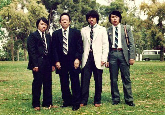 Four Hmong men in suits posing in a park.