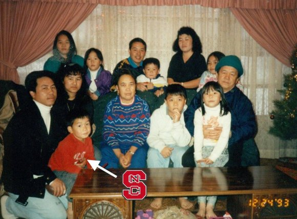 A large Hmong family poses in a living room.