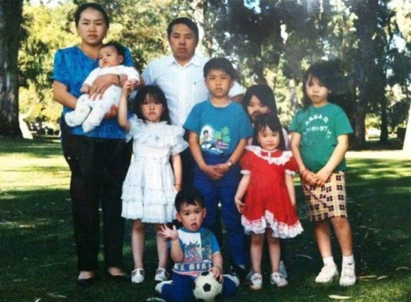 A Hmong family of 9 posing outside.