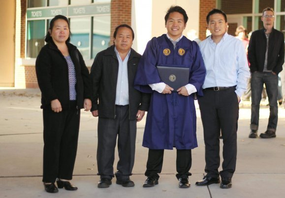 A young Hmong student with his family at graduation.
