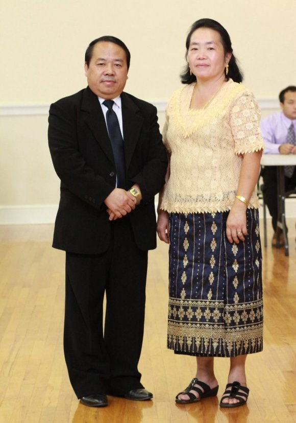A middle-aged Hmong man and woman posing for a portrait.