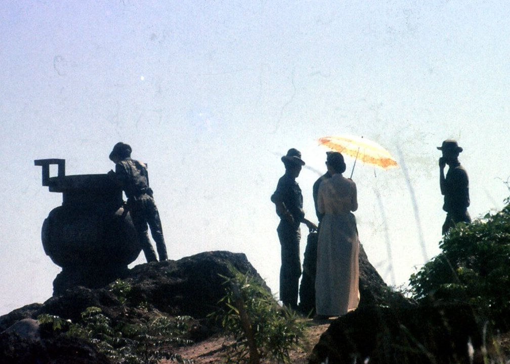 Silhouettes of a group of men and women on a mountain. The woman is holding an orange parasol.