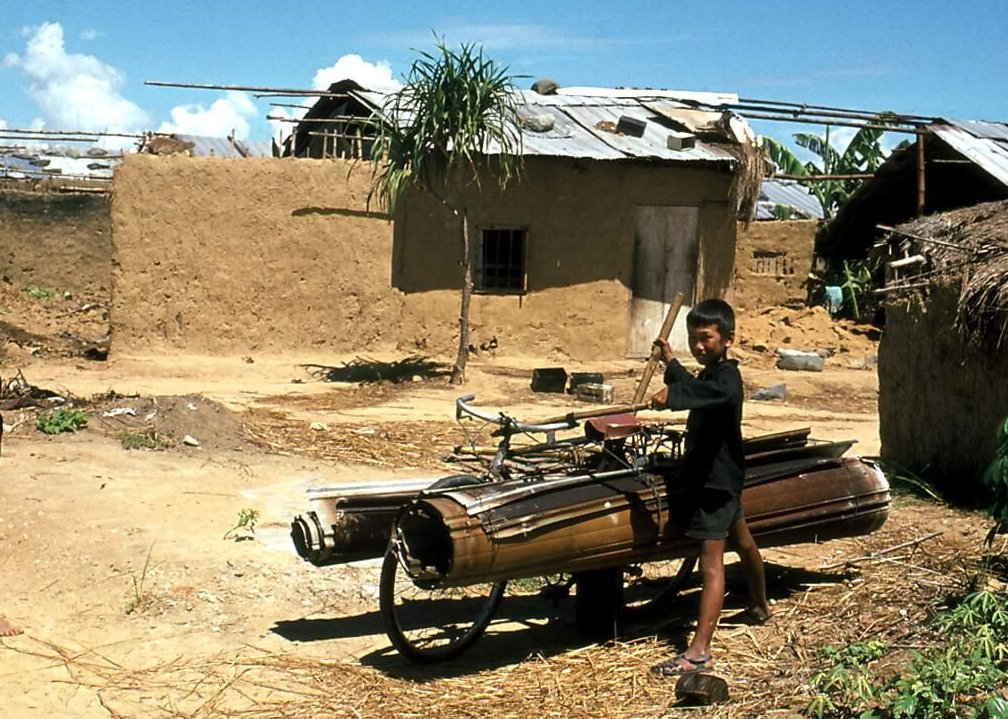 A young asian child standing amid tin and straw shacks, with tin rolled up and attached to his bicycle.