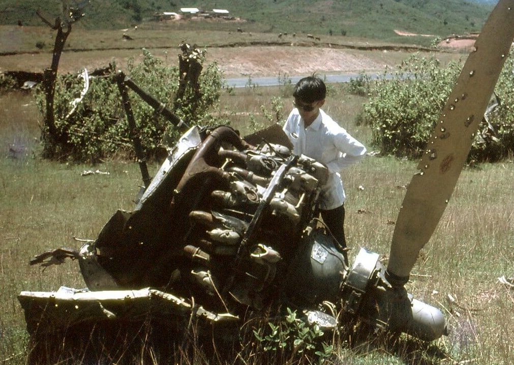 A young Asian man in a field, trying to push a propeller that had fallen from an aircraft.