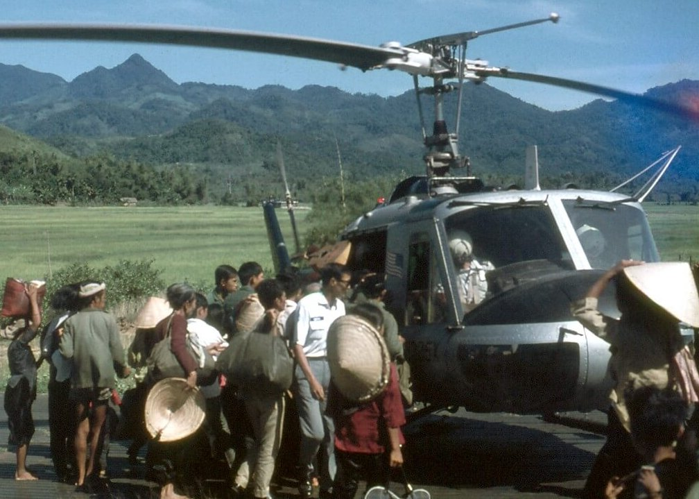 Asian civilians with bags and conical straw hats gathered around a helicopter with an American flag on it. Mountains in the background.