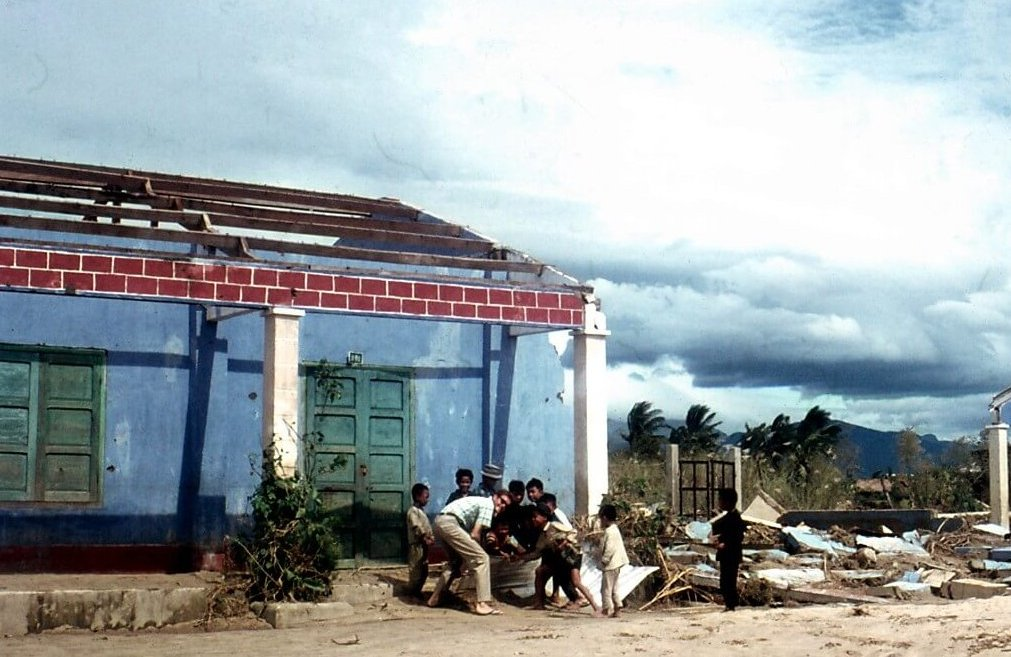 A young American man and several young Asian children crouching outside a blue, green, and red building.