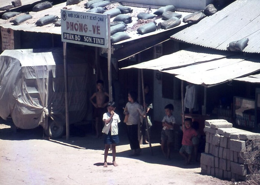 Asian children standing outside tin shacks with sandbags on the roofs.