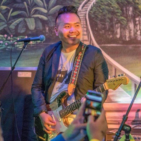 A young Hmong musician plays an electric guitar.