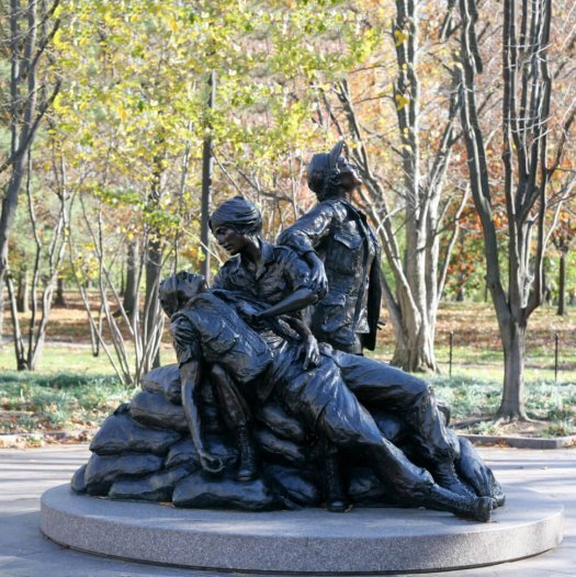 A bronze statue of three nurses helping a wounded soldier.