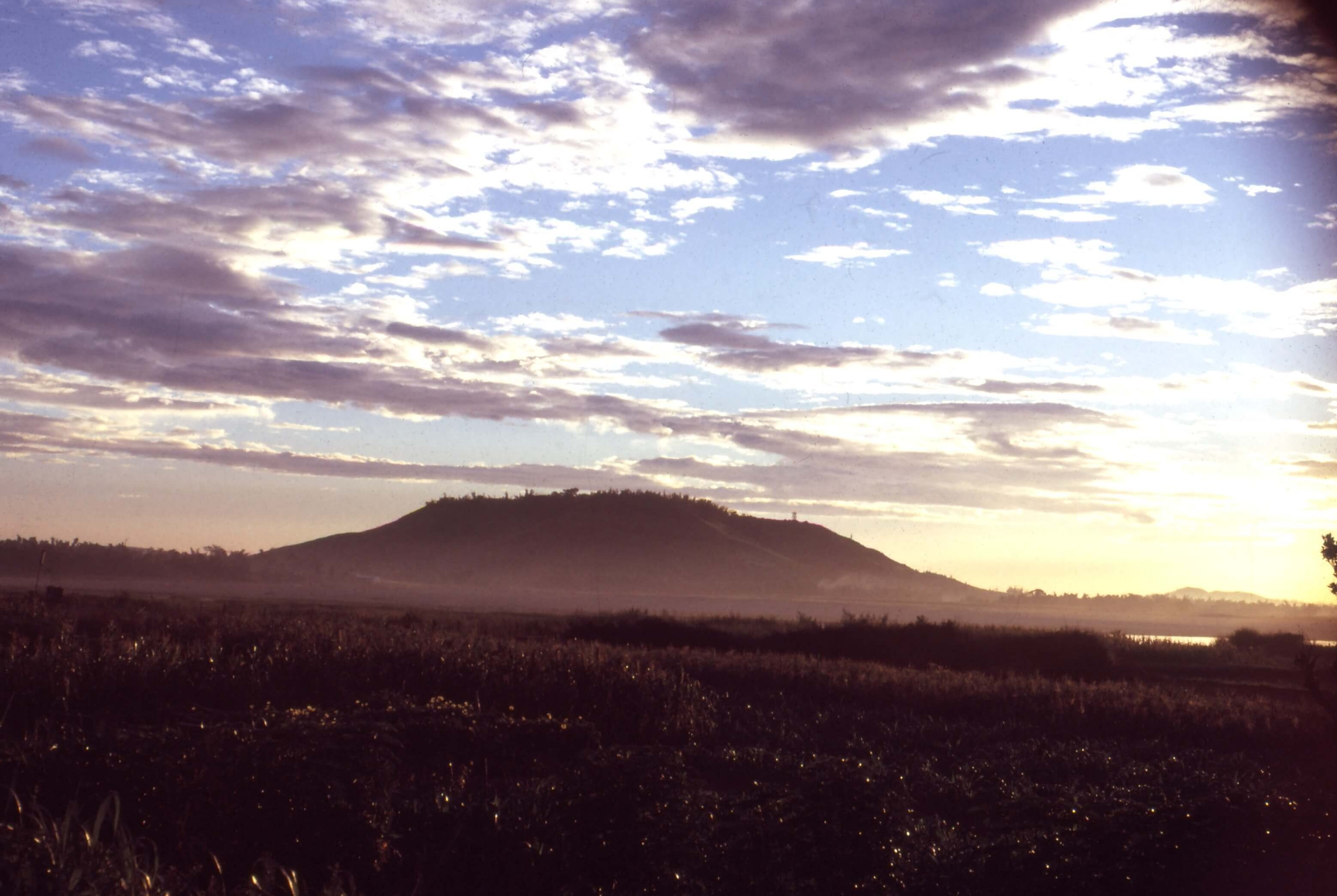 A field in the foreground, a foggy mountain in the background, and a sunrise.