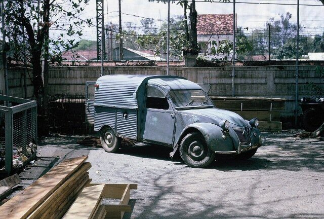 An old vehicle parked in a courtyard with dappled shade.