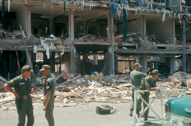 4 soldiers standing outside a bombed-out hotel. Debris is on the street and you can see through the building.