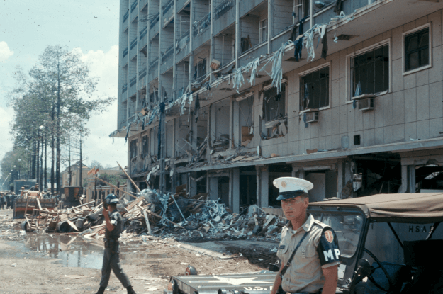 2 soldiers standing outside a bombed-out hotel. Debris litters the street.