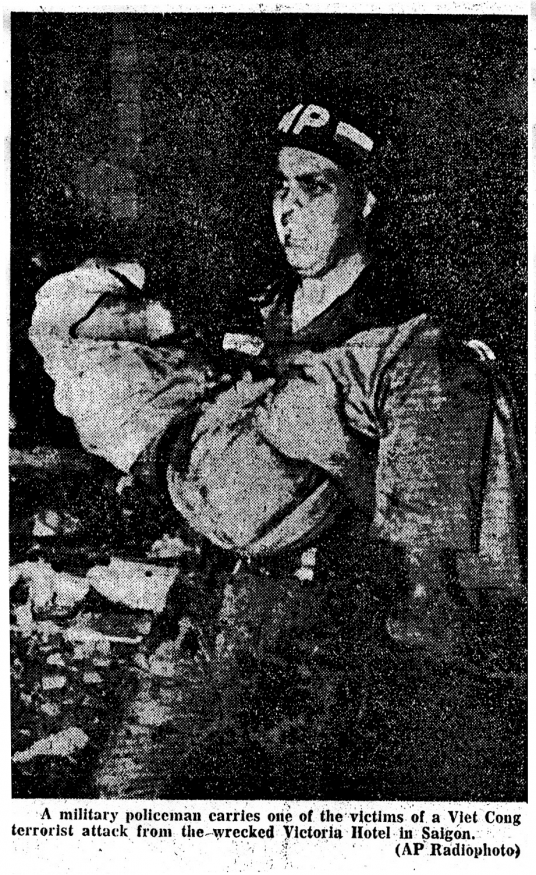 "Newspaper clipping with an AP photo and caption: ""A military policeman carries one of the victims of a Viet Cong terrorist attack from the wrecked Victoria Hotel in Saigon."""