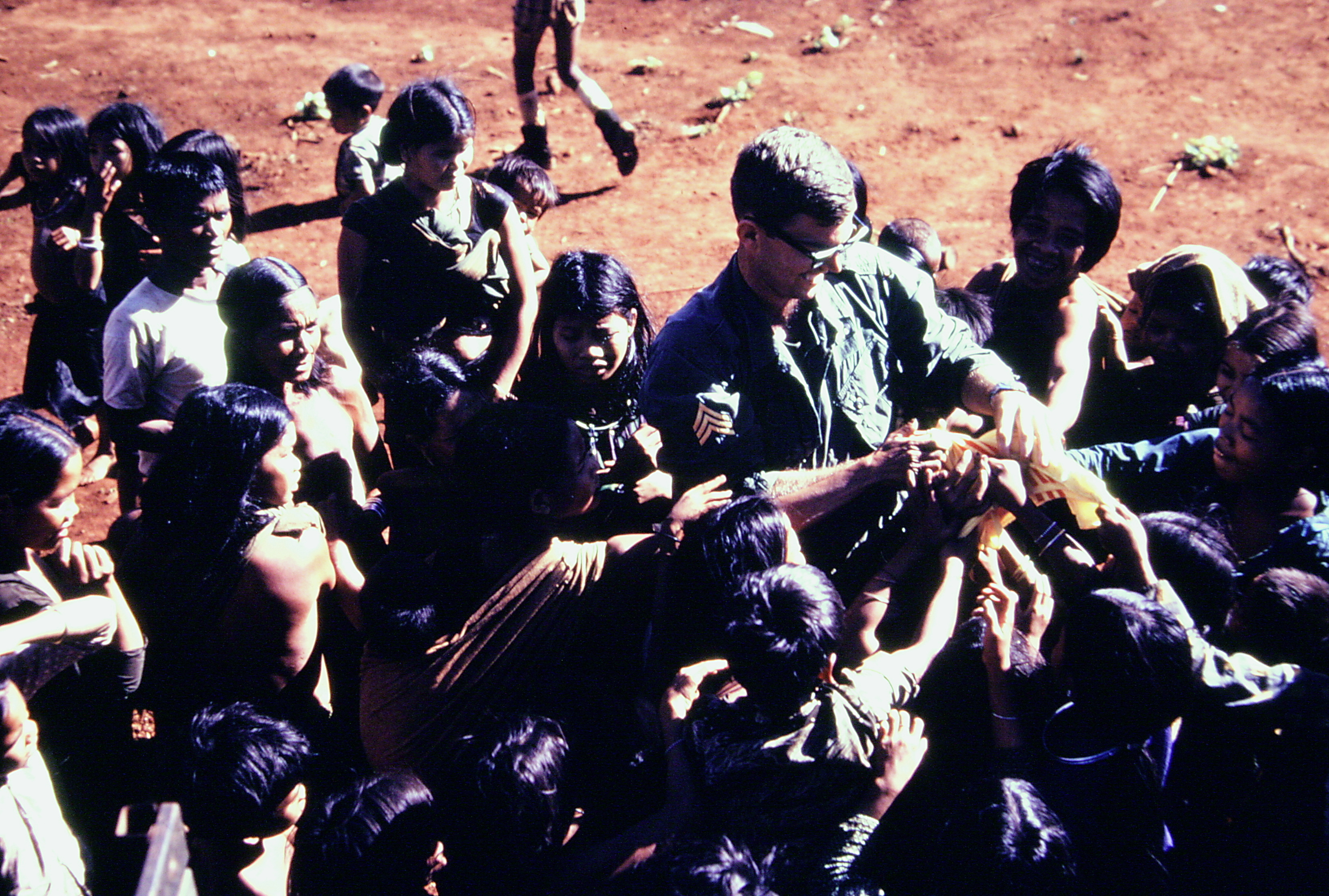Young soldier surrounded by young Montagnard children in a military camp.