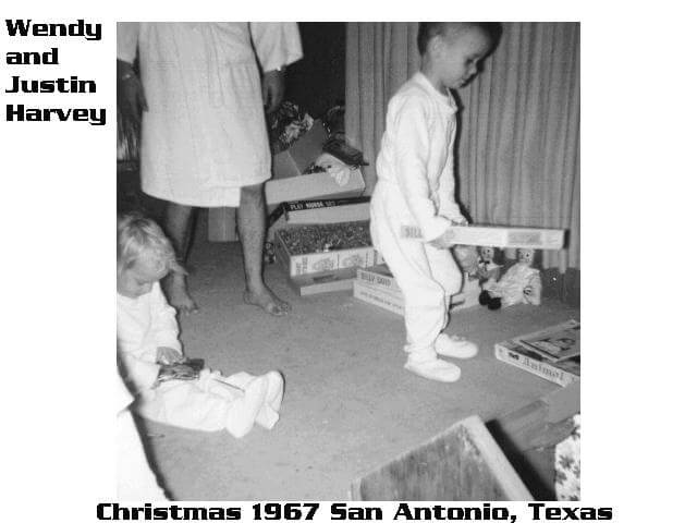 "Two young children in pajamas opening presents. Text in margins says ""Wendy and Justin Harvey, Christmas 1967 San Antonio, Texas."""
