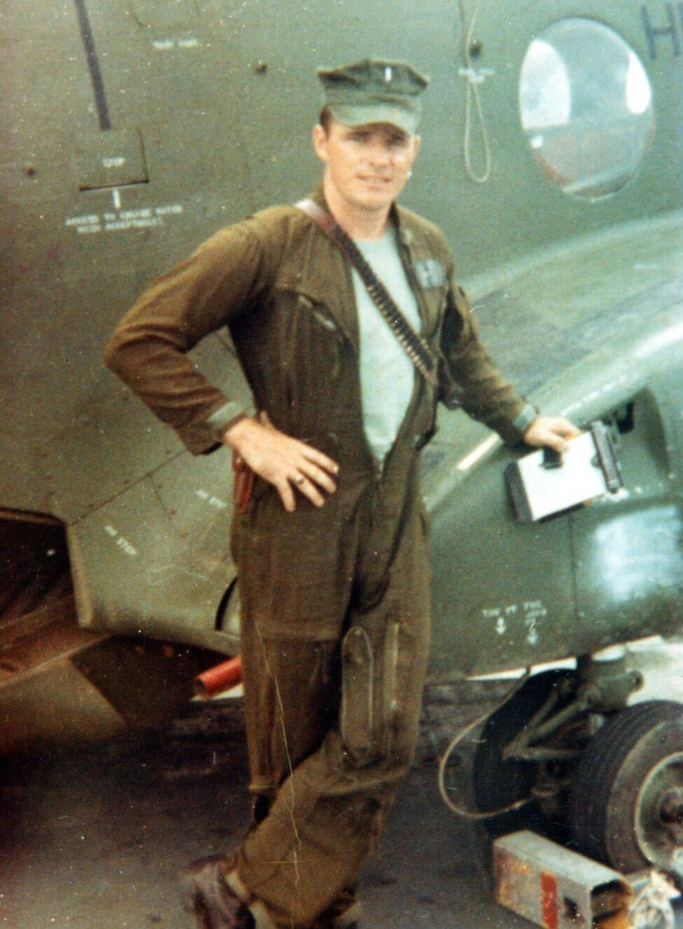 A young man standing in front of CH47, wearing a jumpsuit and a cap.