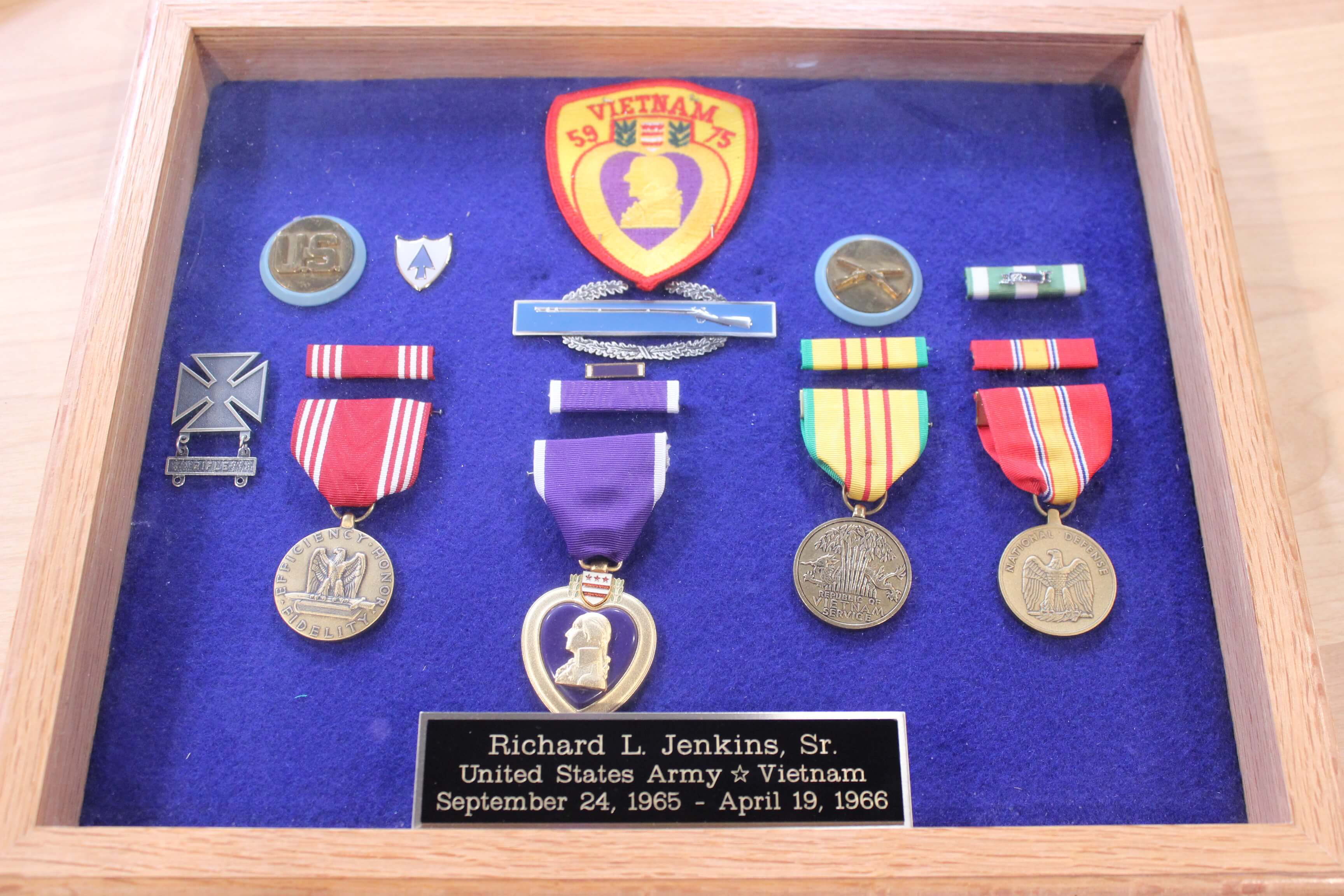 "A wooden case with purple felt and various pins, medals, patches and buttons, including a purple heart. Placard on outside reads ""Richard L. Jenkins, Sr. US Army, September 24-1965 - April 18, 1966""."