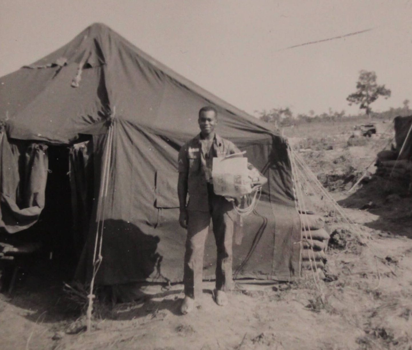 An African American soldier, standing outside a tent.