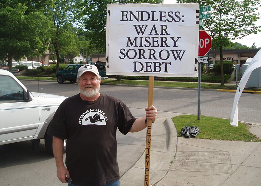 "Contemporary photo of an older gentleman in a black Veterans for Peace t-shirt and ball cap, holding a sign that says ""Endless War, Misery, Sorrow, Debt; Let's Try Peace""."