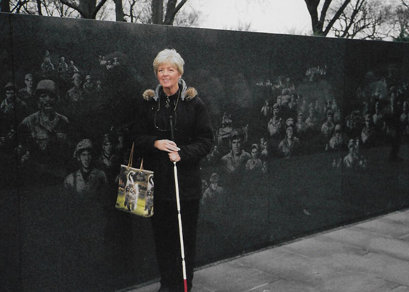 Older woman with cane, standing by the Vietnam War Memorial.