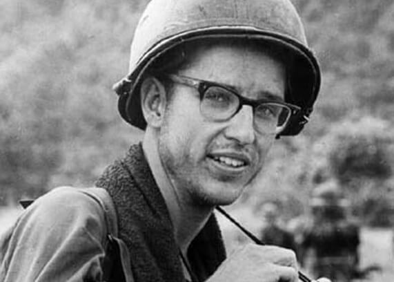 A young soldier in glasses and a helmet, with a camera around his neck.