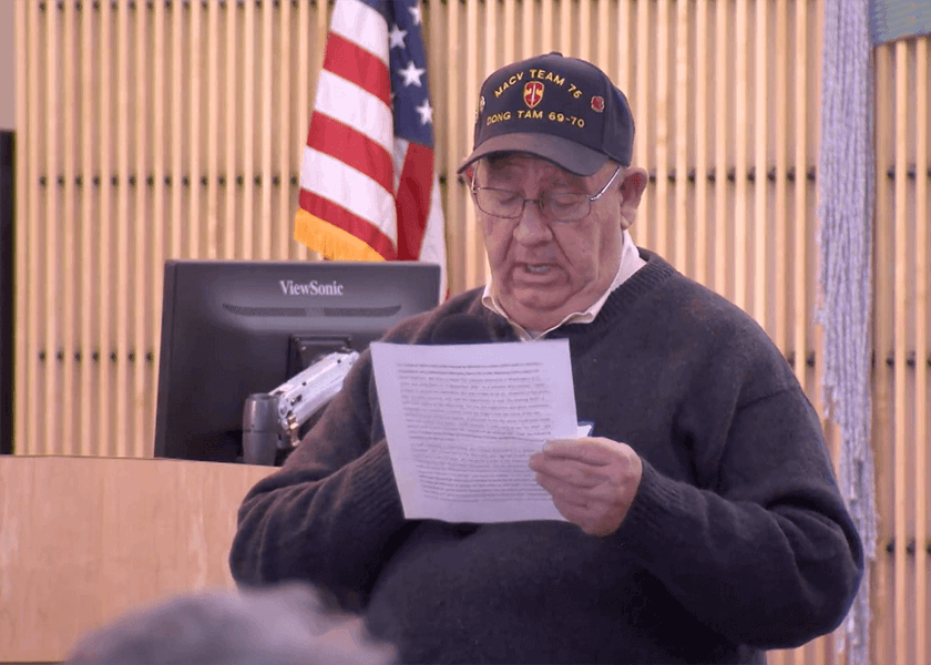 Contemporary image of a man in a MACV 75 Vietnam veteran ball cap and reading from a piece of paper.