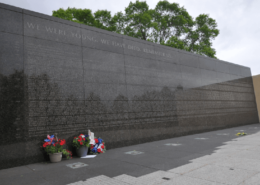 Vietnam Memorial on a cloudy day, two bouqets leaned up against the wall.