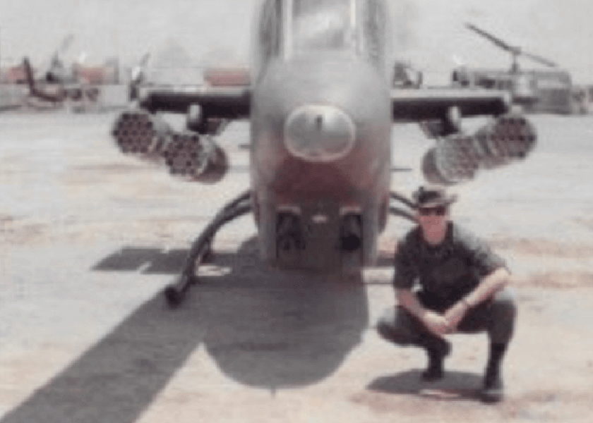 Young soldier crouching next to a military aircraft.