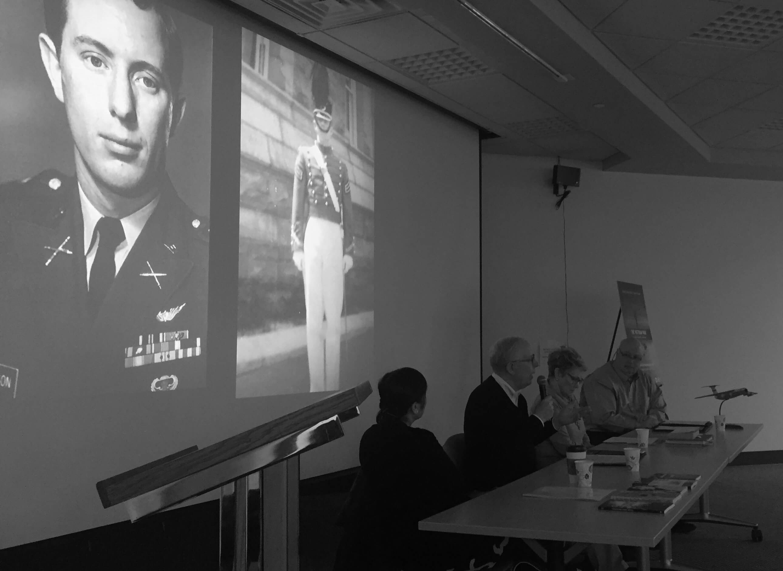 Black and white photo of four people at a table and photos projected behind them of a soldier.