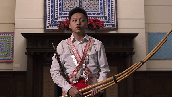 Contemporary image of a young Hmong man holding a reed instrument - qeej.