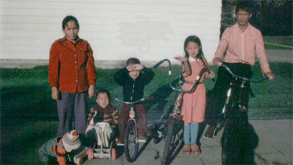 A Hmong family of 6 posing outside a building.