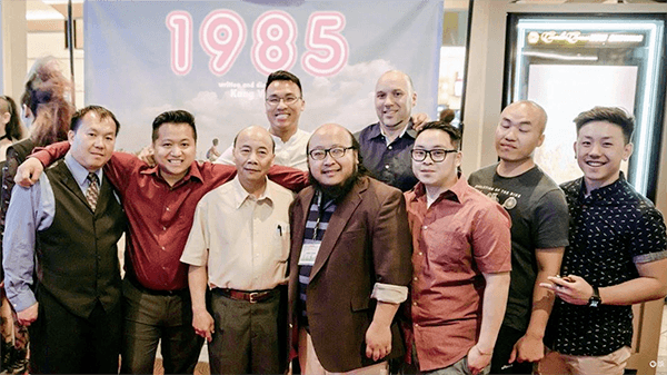"Contemporary photo of a group of Hmong men standing in a movie theater lobby in front of a poster that says ""1985"" in pink bubble lettering."