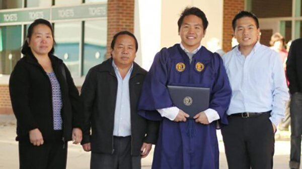 Contemporary photo of a Hmong family of 4, one of the sons is wearing a graduation gown and holding a diploma.
