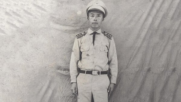 A young Hmong soldier standing against a blank sheet backdrop.