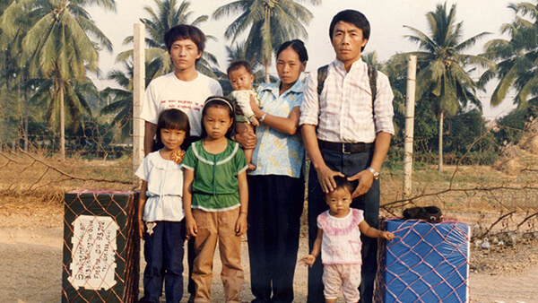 A Hmong family of 7 standing outside with luggage.
