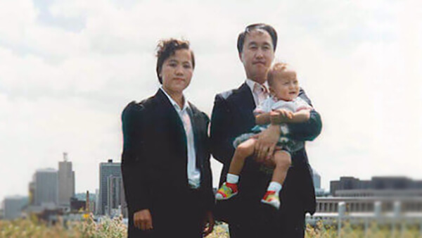 A mother and father standing outside with a cityscape in the background. The father holds an infant in his arms.