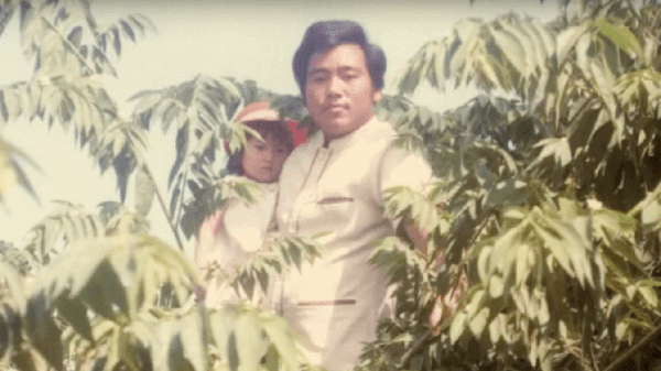 A Hmong father holding his infant daughter, standing amid greenery.