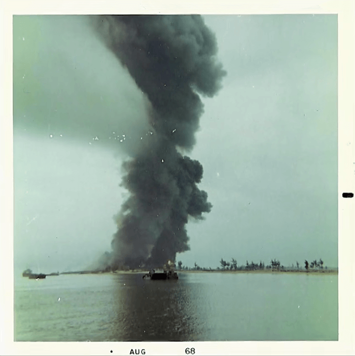 "A large plume of dark smoke rising into the sky. Water and a small boat in the foreground; text on the photo margins reads ""Aug 68""."