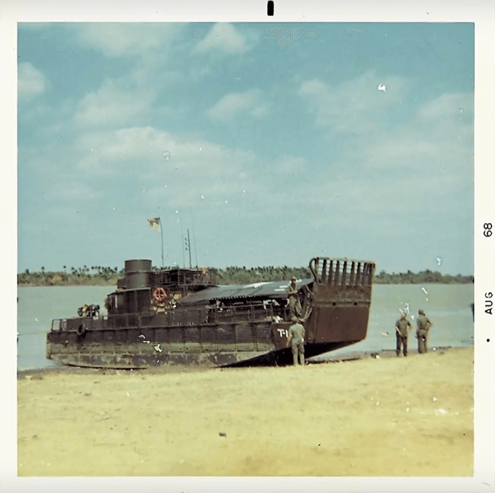 "A small, broad boat that is pulled up to shore. Three soldiers stand nearby. Text on photo margins reads ""Aug 68""."