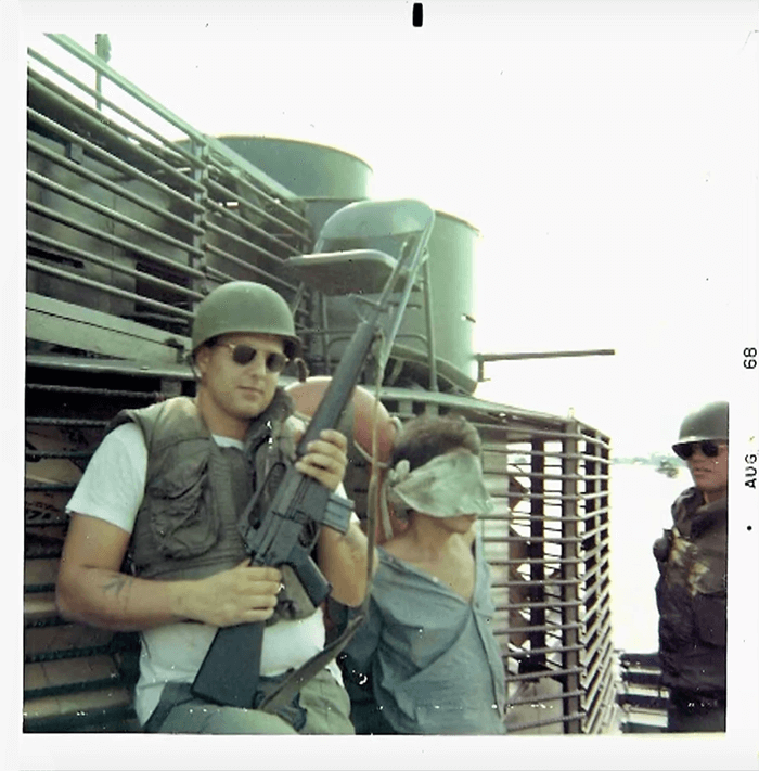 "A young soldier wearing sunglasses and holding a rifle poses next to an Asian man who is blindfolded. Text on photo margins says ""Aug 68""."