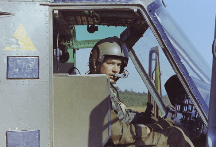 A young pilot in his helicopter, looking out towards the camera.
