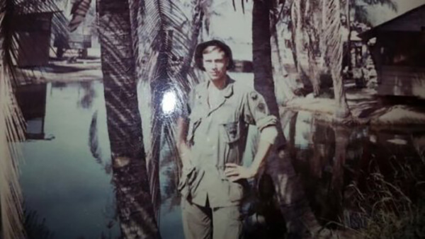 A young soldier with his hands on his hips, standing amid palm trees.