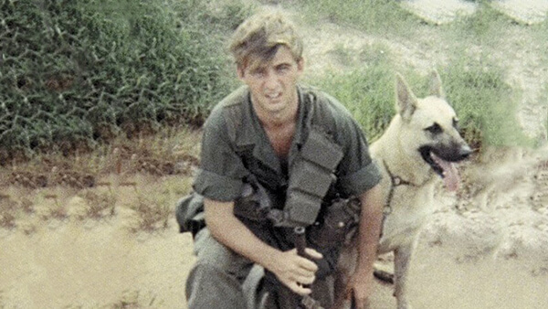 A young soldier crouching down with his German Shepherd scout dog.
