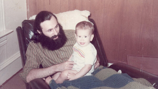 A father with a large beard holding and looking at his son, who is sitting on his lap.