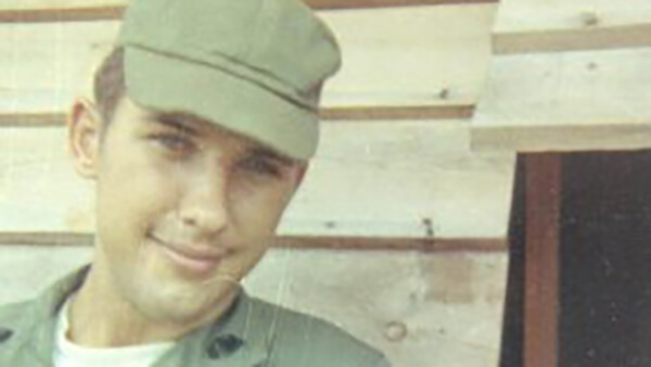 A young soldier with a green cap and slight smile on his face.
