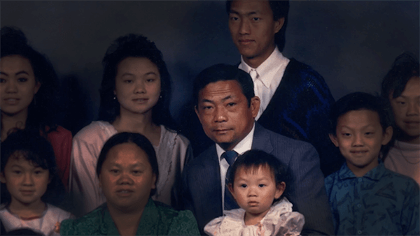 Professional portrait of a large Hmong family. The patriarch is well lit and the other family members are more dimly lit.