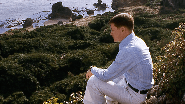 A young man in civilian clothes sitting and peering out onto a body of water.