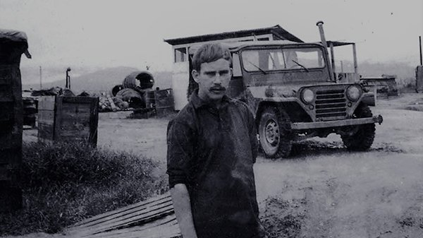 A somber looking young man standing outside, a Jeep in the background.