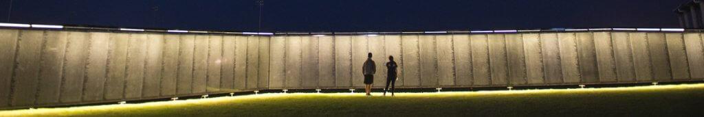 Vietnam Veterans Memorial replica lit up at night.